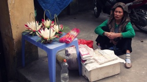 "(The old lady sells in front of Mau temple. Its name means ""The temple of the mother of the forest"""